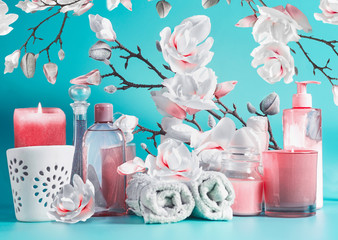 Spa beauty setting with tools: cream, towels, serum, burning candles, lotion , standing on pastel blue table at white pink blossom background. Salon wellness therapy treatments and equipment.