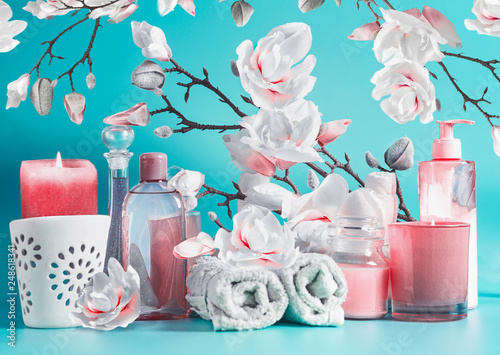 Spa beauty setting with tools: cream, towels, serum, burning candles, lotion , standing on pastel blue table at white pink blossom background. Salon wellness therapy treatments and equipment. © VICUSCHKA