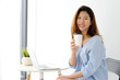Young asian woman holding a coffee cup with smiling face, positive emotion while working with laptop computer, lifestyle, working from home concept