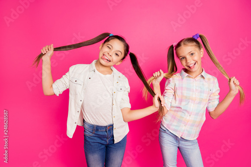 Leinwandbild Motiv Close up photo two pretty little age girls holiday having fun childish glad tongue out mouth blinking playing wearing casual jeans denim checkered plaid shirts isolated rose vivid vibrant background