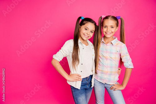 Leinwandbild Motiv Close up photo two small little age girls best friends buddies hugging toothy smiling sweet wearing casual jeans denim checkered plaid shirts isolated rose vivid vibrant bright background