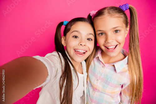 Leinwandbild Motiv Close up photo two small little age she her girls make take summer camp selfies for relatives bonding glad wearing casual jeans denim checkered plaid shirts isolated rose vibrant bright background