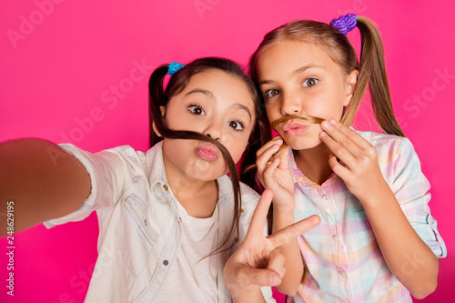 Leinwandbild Motiv Close up photo two small little age she her girls moustache pretend make take summer camp selfies v-sign wearing casual jeans denim checkered plaid shirts isolated rose vibrant bright background