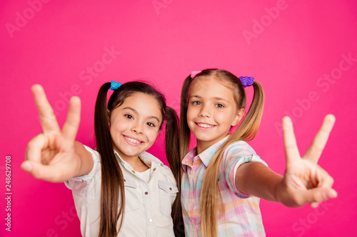 Leinwandbild Motiv Close up photo two small little age she her girls hands arms palms show v-sign say hi mom dad parents wearing casual jeans denim checkered plaid shirts isolated rose vibrant vivid background