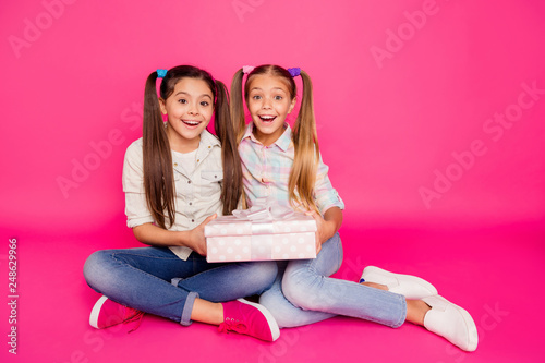Leinwandbild Motiv Close up photo two little age she her girls holding both hands arms one large giftbox best friends sit floor wear casual jeans denim checkered plaid shirts isolated rose vibrant vivid background