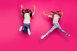 Leinwandbild Motiv Full length body size rear back behind view of two crazy cheerful cheery positive pre-teen girls having fun in air isolated over bright vivid shine pink background