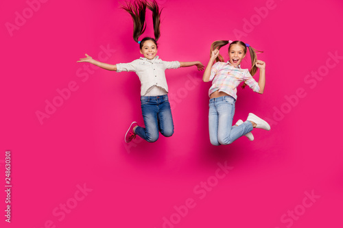 Leinwandbild Motiv Full length body size photo two little age she her girls jumping high win school competition cheerleaders wear casual jeans denim checkered plaid shirts isolated pink rose vibrant vivid background