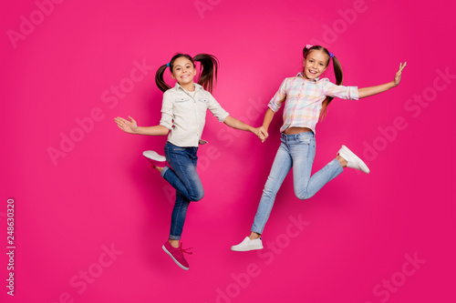 Leinwandbild Motiv Full length body size photo two little age she her girls hand arm jump high win school competition cheerleaders wear casual jeans denim checkered plaid shirts isolated pink vibrant vivid background