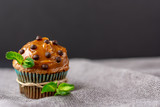chocolate muffin, easter cake, caramel sauce, chocolate drops, chocolate cake on gray napkin. served with mint in rustic style. - 248631715
