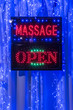 Leinwanddruck Bild - A 'Massage Open' sign hanging in the window of a massage palour with blue, red and green LED lights.