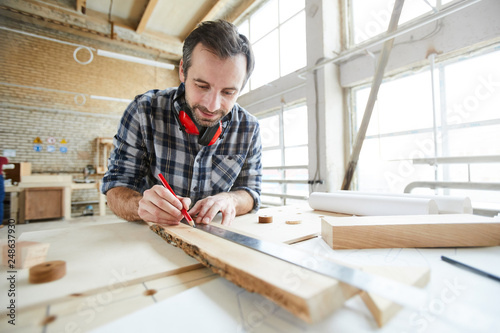 Content handsome middle-aged carpenter with stubble wearing ear protectors on neck drawing straight line with ruler while working with wooden plank - 248637930