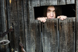 Woman looks out of the wooden shed windows. - 248639746