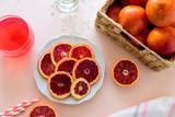 Glass of fresh blood orange juice on pink background. Selective focus
