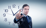 Businessman in a suit shows fingers on the clock. Clock on wall. Concept price time.