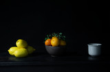 lemon orange fruit classical still life on black table with white ceramic cup food background
