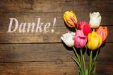 Blumenstrauß aus Tulpen auf altem Holz mit Wort Danke