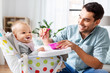 Leinwanddruck Bild - family, food, eating and people concept - happy father feeding little baby daughter sitting in highchair with puree by spoon at home