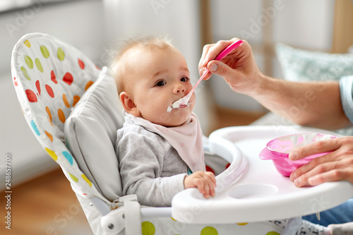 family, food, eating and people concept - father feeding little baby sitting in highchair with puree by spoon at home © Syda Productions