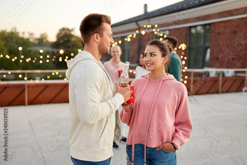 Foto Murales leisure, celebration and people concept - happy friends with non alcoholic drinks at rooftop party in evening