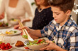 food, eating and people concept - close up of boy with salad bowl at family dinner party - 248659994