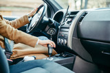young woman hand on gear shift stick in car