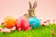 Leinwandbild Motiv Osterhase und Ostereier zu Ostern auf Wiese