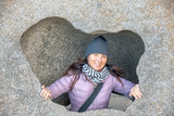 Happy woman embracing a big rock from inside - 248678175