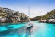 Leinwanddruck Bild - Beautiful beach with sailing boat yacht, Cala Macarelleta, Menorca island, Spain. Yachting, travel and active lifestyle concept