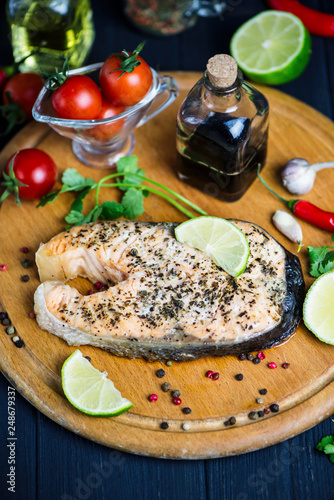 red fish salmon baked with spices and lemon on a wooden board - 248679337
