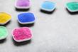 Colorful holi powder in bowls on grey background