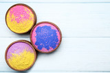 Colorful holi powder in bowls on wooden table - 248684782