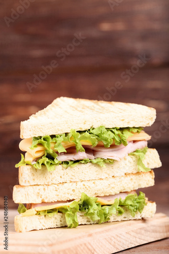 Foto Murales Tasty sandwiches with cutting board on brown wooden background