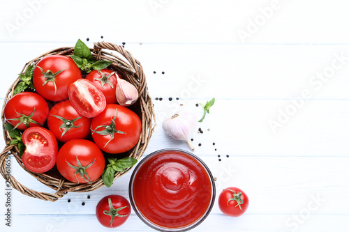 Ketchup in bowl with basil leafs and garlic on wooden table