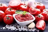 Ketchup in bowl with basil leafs and salt on black wooden table - 248686747
