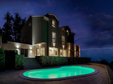 night view of the exterior of a modern villa in the foreground illuminated swimming pool - 248687912