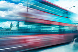 London Red Bus speeding up in London. Blurred view with city skyline on background - 248693518