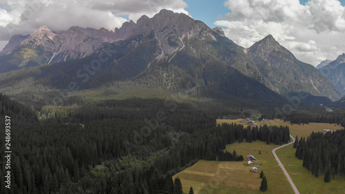Panoramic aerial view of Italian Alps with mountains and woods