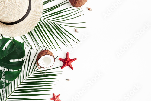 Summer composition. Tropical palm leaves, hat, coconut on white background. Summer concept. Flat lay, top view, copy space © Flaffy