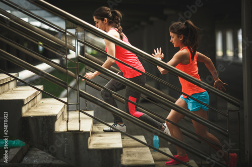 Two female friends runners jogging on the city street.They runs up the stairs.City environment.