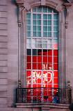 Das kunstvoll gefertigte Gussgeländer eines kleinen Balkon mit nostalgischem Mosaikfenster. - 248711151