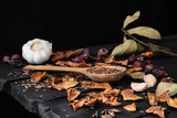 Garlic, dried fruit and seeds in dark rustic background. Artistic photo of garlic and dry fruit on old black table shot in low key ciaroscurro style - 248711725