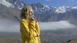 happy woman in a yellow coat against the backdrop of the mountains