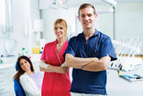 Two young dentists with the patient looking at camera while standing in a dental clinic.