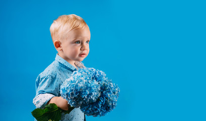 Childrens day. Small baby boy. Summer. Mothers or womens day. New life concept. Spring holiday. Little boy at blooming flower. Spring flowers. Childhood. Spring collection