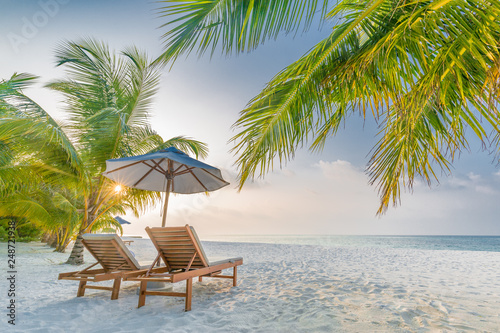 Foto Murales Tropical beach resort hotel background as summer landscape with lounge chairs and palm trees in sun rays and calm sea for beach banner. Luxury vacation and holiday destination concept