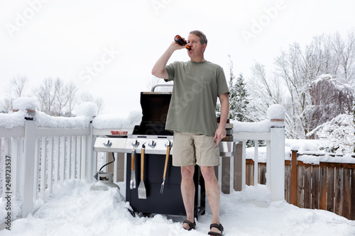 Leinwanddruck Bild Mature man getting ready to grill while drinking beer during winter season