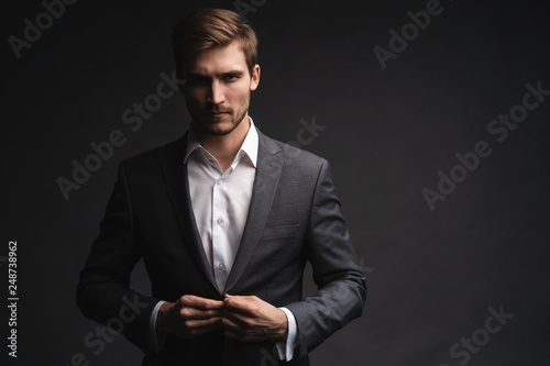 Portrait of serious handsome man in gray suit buttoning jacket © opolja