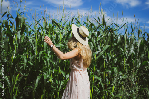 Foto Murales Beautiful woman with long blond hair in hat walking in cornfield, summer, Latvia