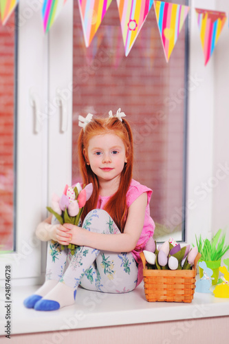 Foto Murales child girl with red hair sitting on a windowsill holding a bouquet of tulips in her hands and smiling. March 8, Easter, spring.