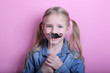 funny young blond girl ready for party over pink background. Lifestyle and people concept.